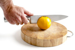 Sharp stainless steel  knife cutting into orange Royalty Free Stock Photos