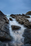 Sharp stones, rocks washed by the waves blurred. Stock Photos
