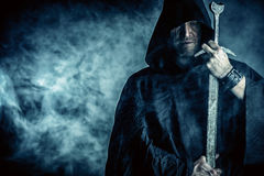 Sharp sword. Portrait of a courageous warrior wanderer in a black cloak and sword in hand. Historical fantasy Royalty Free Stock Photos