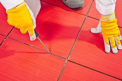 Sharp tool clean spaces between tiles. Remove tile adhesive debris dust particles royalty free stock photography