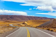 Sharp turn of the road. In the Argentine prairie. Summer day in February. The concept of active and extreme tourism Royalty Free Stock Images