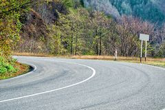 A sharp turn on the road between green trees and small mountains. Close-up. Without people stock images