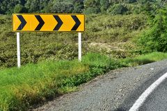 Sharp turn road sign. Bright yellow road sign warning before sharp turn on countryside road stock photos