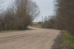 Sharp turn with warning sign on a gravel road. Stock Photos