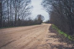 Sharp turn with warning sign on a gravel road. Stock Images