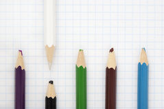 Sharp  white pencil. And blunt colored pencils on a writing-book leaf Stock Images