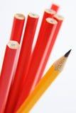 Sharp Yellow Pencil. Close up shot of a sharp yellow pencil amongst unsharpened red pencils. Narrow depth of field royalty free stock photos