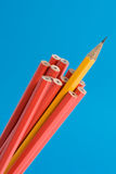 Sharp Yellow Pencil. Close up shot of a sharp yellow pencil amongst unsharpened red pencils. Narrow depth of field, shot against a blue background Stock Photos
