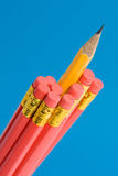 Sharp Yellow Pencil Amongst Red Pencils. Close up shot of a sharp yellow pencil amongst red pencils with erasers on the end. Shot against a blue background Royalty Free Stock Photography