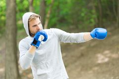 Sharpen defending skill. Sportsman concentrated training boxing gloves. Athlete concentrated face sport gloves practice. Defending skills nature background royalty free stock photography