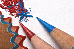 Sharpen the pencils. Green, red and blue pencil being sharpened on a white piece of textured paper Stock Photo