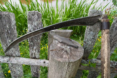 Sharpen scythe. Scythe and whetstone supported on wooden fence Royalty Free Stock Image