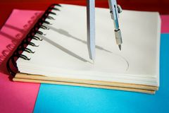 Sharpened上色了铅笔与在蓝色背景的一个空白的笔记薄一起说谎 库存图片