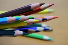 Sharpened color pencil on brown wood background. Sharpened color pencil on blurred brown wood background for web element or drawing object Stock Images