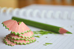 Sharpened color pencil and shavings on opened notebook Royalty Free Stock Photography