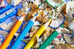 Sharpened colored pencils sharpener and pencil shavings Royalty Free Stock Photography