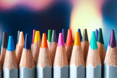 Sharpened colored pencils. A stack of colored pencils. Ready to paint. Colored pencils on a colorful background. Royalty Free Stock Images