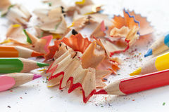 Sharpened colourful pencils and wood shavings. Close up Royalty Free Stock Images