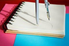 Sharpened färgade blyertspennor ligger samman med en tom notepad på en blå bakgrund fotografering för bildbyråer