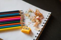 Sharpened färgade blyertspennor, vässaren och shavings Arkivfoto