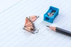 Sharpened pencel with sharpener. Close-up sharpened pencil with sharpener on white lines paper book page stock photo