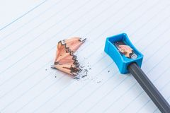 Sharpened pencel with sharpener. Close-up sharpened pencil with sharpener on white lines paper book page stock images