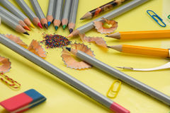 Sharpened pencil, eraser, compass, paper clips on yellow backg Royalty Free Stock Photos