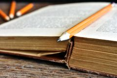 Sharpened Pencil and Old Book. A close up image of a single sharpened pencil on an old open book Stock Photos