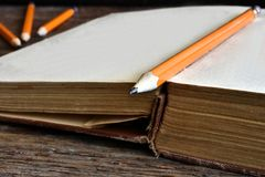 Sharpened Pencil and Old Book. A close up image of a single sharpened pencil on an old open book Stock Photo