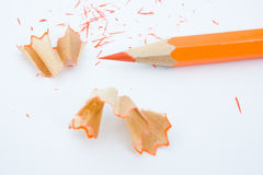 Sharpened pencil and wood shavings. Sharp orange pencil and shavings isolated on white background. Macro with extremely shallow depth of field Stock Photos