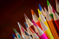 Sharpened tips of color pencils against red wood background Royalty Free Stock Images
