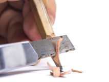 Sharpened wooden pencil by cutter knife  close-up on white backg Royalty Free Stock Image