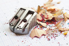Sharpener and coloring  pencil shavings on notebook Stock Image