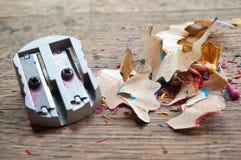 Sharpener and pencil shaving on wooden desk Stock Images
