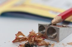Sharpener, sharpened pencil, crossword in the background. Royalty Free Stock Photos