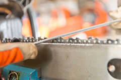 Sharpening a chainsaw. Close up on a man sharpening a chainsaw chain with file stock photos