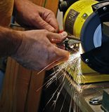 Sharpening. A chisel on grinding machine with sparks fly stock images