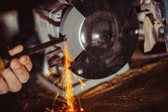 Sharpening the cutter on the machine. Sharpening a chisel on grinding machine with sparks fly royalty free stock photo
