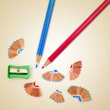 Sharpening colored pencils. Picture of some colored pencils and a pencil sharpener on a beige background, with a retro effect Royalty Free Stock Photography
