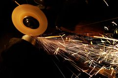Sharpening and cutting metal. Manual sharpening and cutting of metal by abrasive disk machine royalty free stock photography