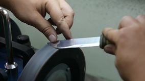 Master sharpens the knife on the machine, so it was sharp stock video footage
