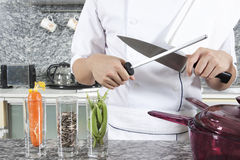 Sharpening a knife. Chef sharpening a knife in the kitchen stock photos