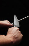 Sharpening a knife. A knife being sharpened against a black background Royalty Free Stock Photography