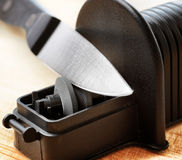 Sharpening of knife in a kitchen Royalty Free Stock Image