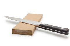 Sharpening a knife on a waterstone. Sharpening or honing a knife on a waterstone. on white stock photography
