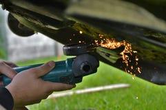 Sharpening mower blades. A mans hands using a grinder to sharpen mower blades stock photo