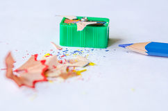Sharpening a pencil against white background. Sharpening a pencil against the white background. Pencil, sharpener and shavings. Close up, top view, space for Royalty Free Stock Images