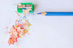 Sharpening a pencil against white background. Sharpening a pencil against the white background. Pencil, sharpener and shavings. Close up, top view, space for Royalty Free Stock Image