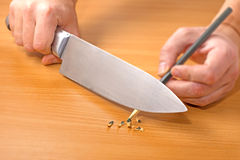 Sharpening a pencil with a knife Royalty Free Stock Photo