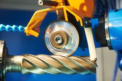 Sharpening rapid steel mill on automatic CNC grinding machine. At factory royalty free stock image